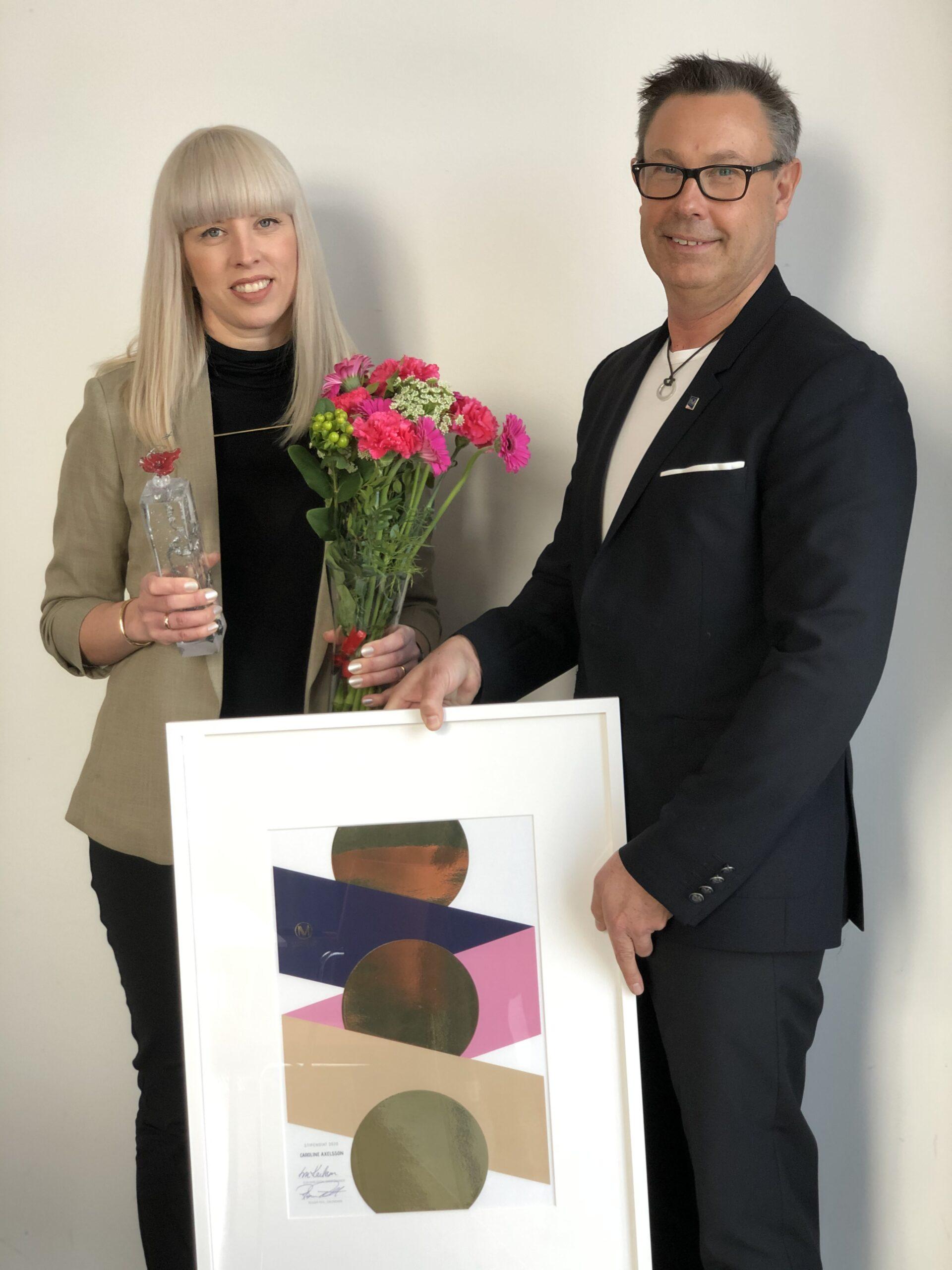 Caroline Axelsson med pris och blommor tillsammans med Roger Pihl